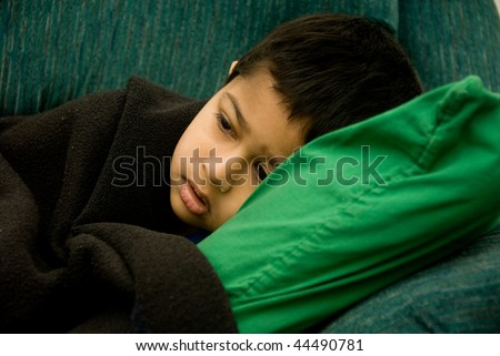 An handsome Indian kid looking very sick - stock photo