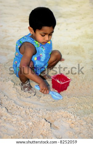 An handsome Indian kid making a sand castle at beach - stock photo