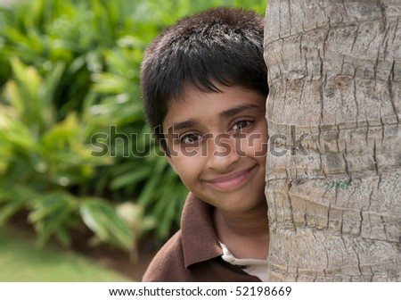 An handsome Indian kid peeping thru the trunk - stock photo