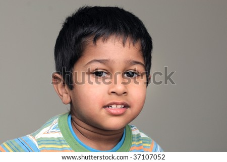 An handsome Indian kid smiling in front of the camera - stock photo