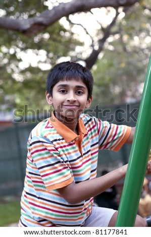 An handsome Indian toddler having fun in the play area - stock photo
