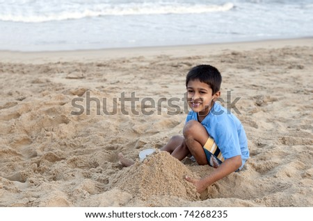 an handsome young indian kid building sand castle at the beach - stock photo