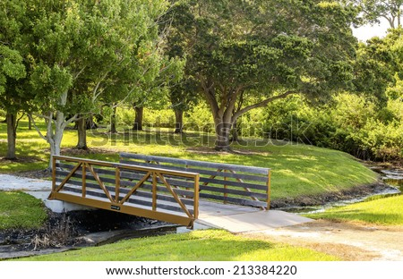 An HDR photo of a bridge and path crossing a creek. - stock photo
