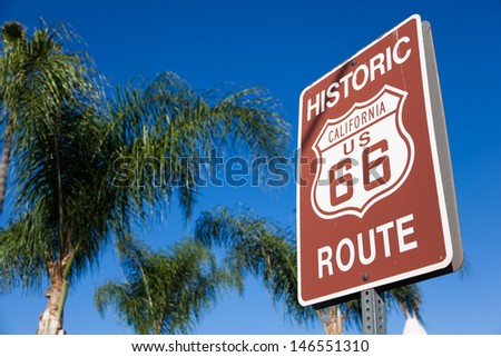 An historic route 66 highway sign with palm tree branches and a blue sky background - stock photo