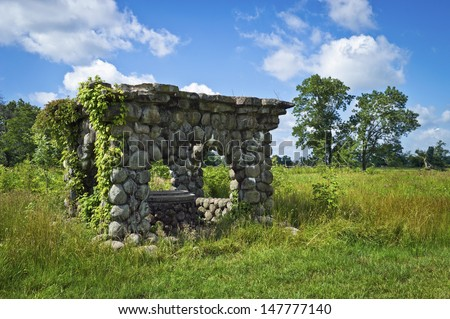 An historic stone gazebo surrounds this well in Duke Farms, a public environmental park in Central New Jersey. - stock photo