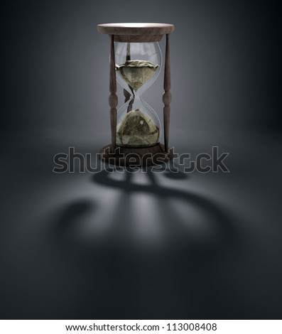 An hourglass casting a shadow of a dollar sign - time is money concept - stock photo