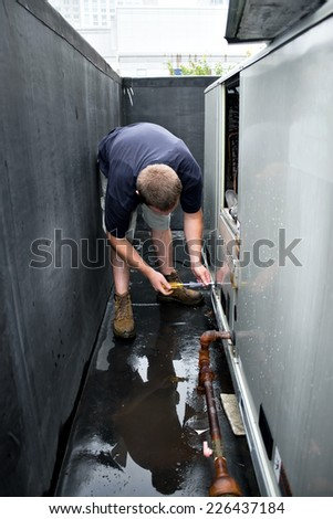 An HVAC heating ventilating air conditioning technician repairing or maintaining a large commercial unit. - stock photo
