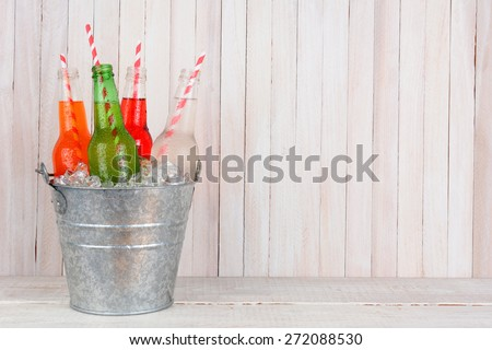 An ice bucket of four different soda bottles with drinking straws in a white wood set. Horizontal format with copy space. - stock photo