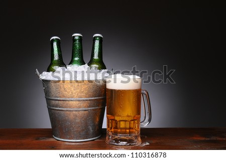 An ice bucket with three green beer bottles next to a full mug of ale on a wet wood surface. Horizontal format with a light to dark gray background. - stock photo