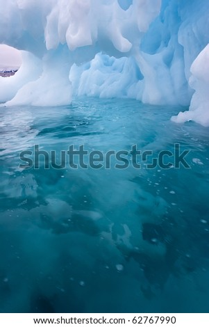 an ice cave carved by the sea in a giant iceberg - stock photo