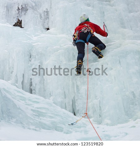 An ice climber makes his way up on a frozen waterfall near Prags, South Tyrol, Italy.