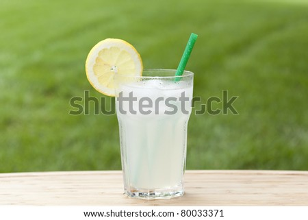 An ice cold lemonade on a wooden board - stock photo