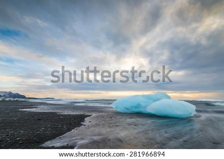 An iceberg on the beach of Jokulsarlon at sunrise time, Iceland - stock photo