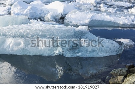 An iceberg reflected in Jokulsarlon glacial lagoon on a sunny winter's afternoon in Iceland