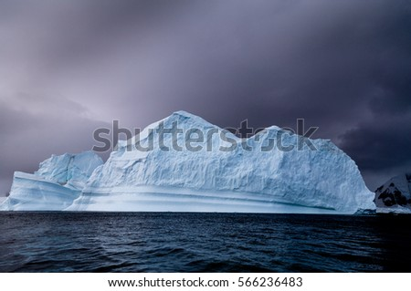 An iceberg shot near Danco Island, Antarctica in low level light and dark clouds.