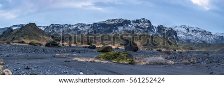 An Iceland mountain range panorama shows the snow-covered mountaintops with dry volcanic landscape and arctic vegetation surrounding the terrain.