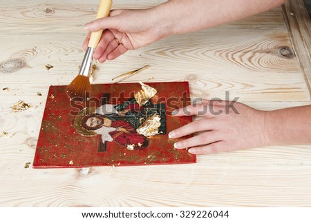 an icon-painter works on  gilded icon - stock photo