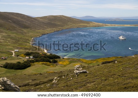 An idyllic bay in the Falkland Islands with a farmhouse by the shore and  cruise ship anchored nearby. - stock photo