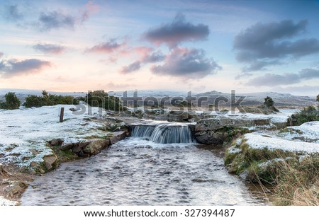 An idyllic winter scene with snow on the ground and a beautiful waterfall, on Dartmoor National Park in Devon
