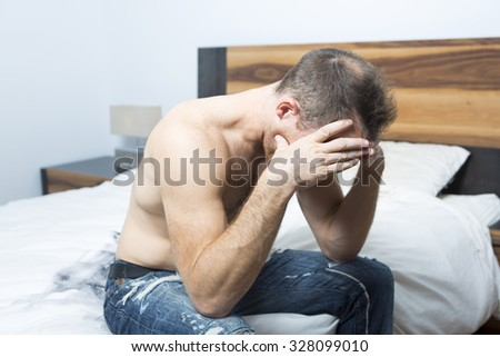 An Ill man sitting on his bed with his head on his hand