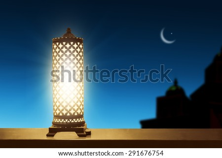 An illuminated ramadan lantern against blue night sky with an crescent moon. - stock photo
