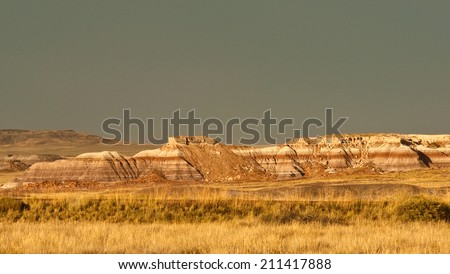 An illuminated ridge set against a stormy sky in Petrified National Forest, Arizona. - stock photo