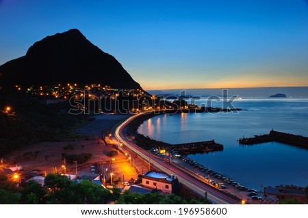 An illuminated road along the shore and a town at the foot of a mountain. - stock photo