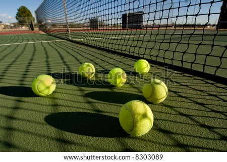 An image depicting the concept of tennis, including the court and balls at sunset. - stock photo