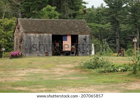 An image of a barn, with an antique thirteen star American flag.  The barn contains many antiques from the late 18th century.