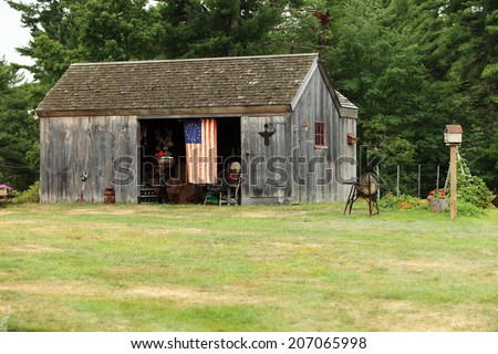 An image of a barn, with an antique thirteen star American flag.  The barn contains many antiques from the late 18th century. - stock photo