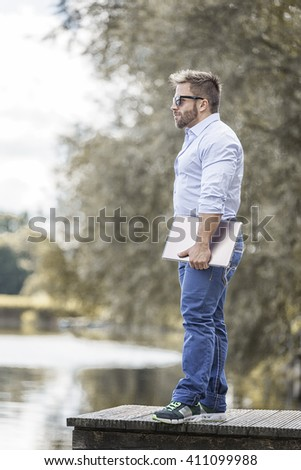 An image of a bearded man at the lake with a notebook