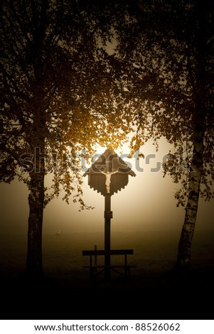 An image of a beautiful cross with fog in bavaria germany - stock photo