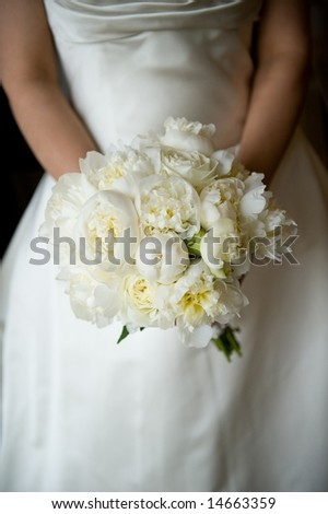 An image of a bride holding her bouquet of peonies - stock photo