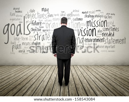 An image of a business man and a strategy text cloud on the wall - stock photo
