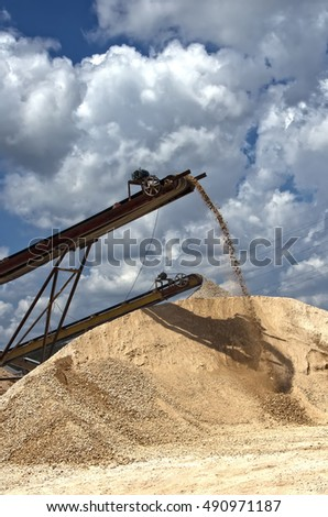 an image of a crusher working. blue sky and a screen working. gravel and a conveyor belt working in a quarry