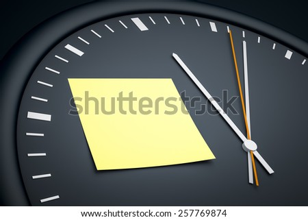 An image of a dark clock with a sticky note