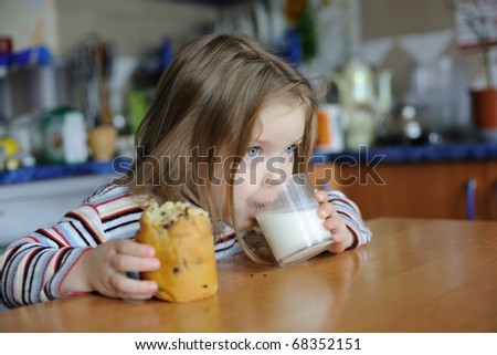 An image of a girl eating cookie with milk - stock photo