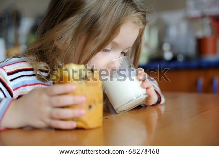 An image of a girl eating sweet cookie with milk - stock photo