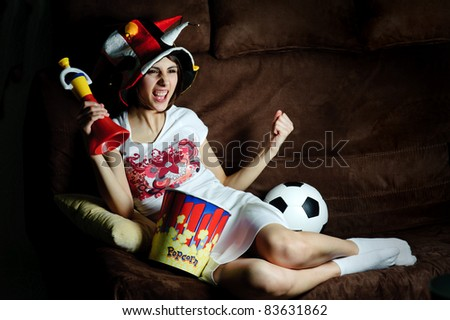 An image of a girl on a sofa watching football on TV - stock photo