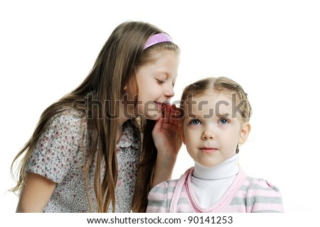 An image of a girl telling a secret to her sister - stock photo