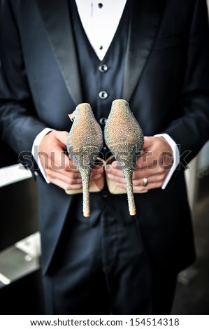 An image of a groom holding bride's shoes - stock photo