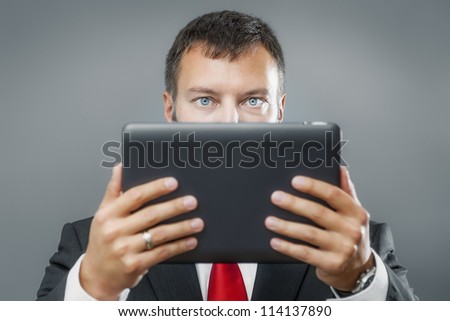 An image of a handsome business man reading his tablet pc - stock photo