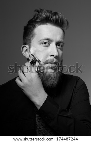 An image of a handsome man with a beard and stylish hairstyle