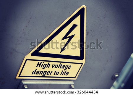 An image of a high voltage warning sign on a metal box. Focus point is on the arrow and image is taken from an angle. Image has a vintage effect applied. - stock photo