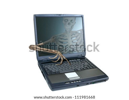 An image of a human skeleton inside a computer trying to reach out of the screen and take over the computer, emblematic of a computer virus or hacker attack. - stock photo