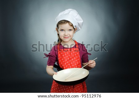 An image of a little girl in white hat with frying pan - stock photo