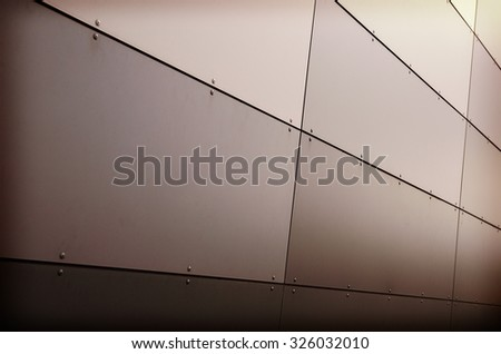 An image of a metal surface on a building wall. Image taken from low perspective angle. Image is nicely suitable for example for backgrounds. Image has a strong vintage effect applied.