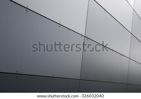 An image of a metal surface on a building wall. Image taken from low perspective angle. Image is nicely suitable for example for backgrounds. Image has a strong vintage effect applied. - stock photo