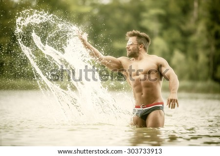 An image of a muscular man in the lake playing with the water