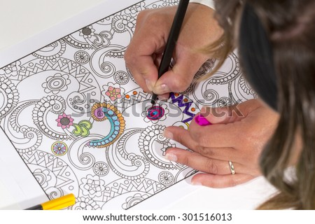 An image of a new trendy thing called adults coloring book. In this image a person is coloring an illustrative and detailed pattern for stress relieve for adults with a color pencil.